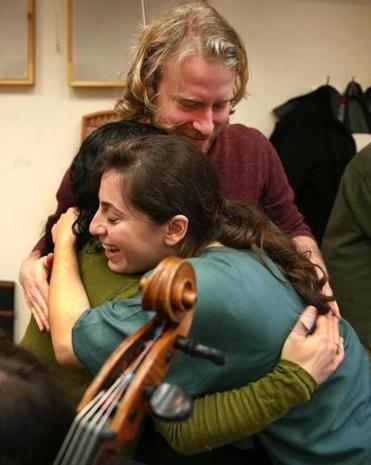 Karen Ouzounian (right) hugs Annie Rabbat and Erik Higgins.